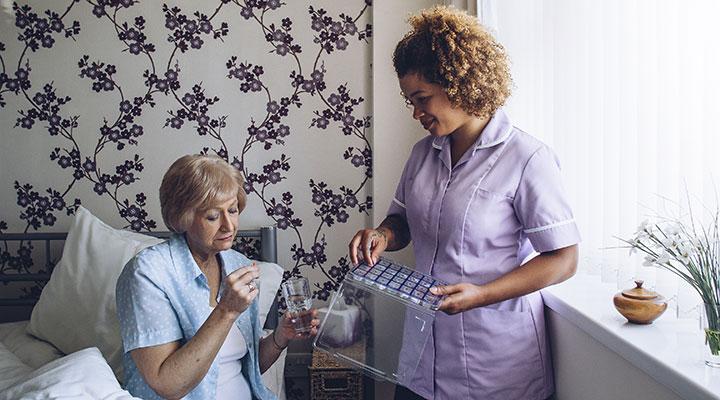 Female carer administering medicine to resident