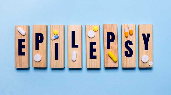 The word EPILEPSY is written on wooden blocks on a blue background near the pills.