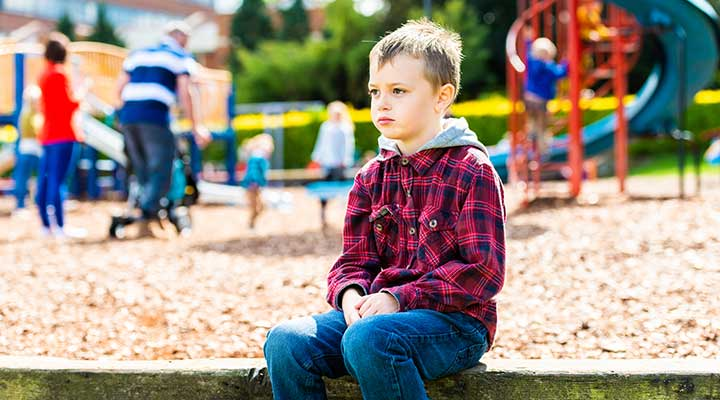 Young boy with Autism sat in a park by himslelf